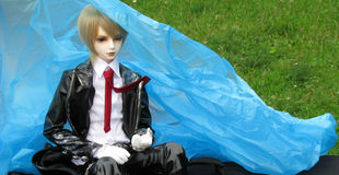 Doll in shiny black jacket hiding from the rain Royalty Free Stock Photography