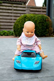 The doll sitting on toy blue car Royalty Free Stock Photo