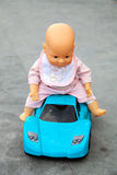 The doll sitting on toy sport car Royalty Free Stock Image