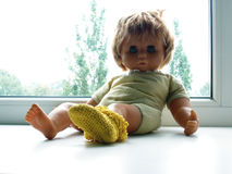 Doll sitting on the window shelf Royalty Free Stock Photography