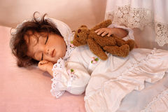 Doll Sleeping with Teddy Bear Stock Photo