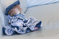 Doll on sofa. Expressionless doll with red hair Royalty Free Stock Image