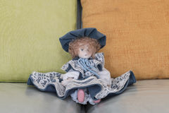Doll on sofa. Expressionless doll with red hair Royalty Free Stock Images