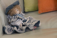 Doll on sofa. Expressionless doll with red hair Royalty Free Stock Photography