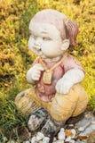 Doll Standbeeldglimlach in zittingspositie Stock Afbeeldingen