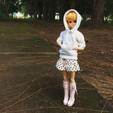 An adorable vintage doll named Flora-chan. The doll is standing alone at the lonely road waiting for someone who will pass by and pick her royalty free stock photography