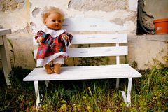 Doll standing on bench Stock Photo