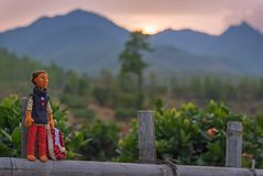 A doll staying on the fence. A doll made of felt staying on the fence against sunset mountain chain Stock Photo