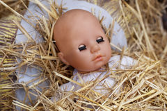 Doll and straw in a manger Stock Photography