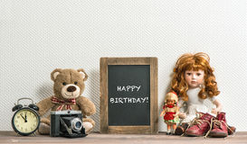 Doll, Teddy Bear, chalkboard and vintage toys. Happy Birthday Royalty Free Stock Photography