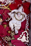Doll toy in a tinsel festive ambience. Toy doll surrounded by beads and other celebratory tinsel Royalty Free Stock Photos
