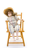 Doll on a wooden chair Stock Photo