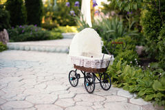 Doll's pram. Vintage doll stroller placed on the stone walkway, alley in a beautiful garden Royalty Free Stock Images