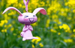 Doll in yellow green background. Little pink rabbit doll in background of yellow rape field,there is a heart picture in the doll which is drew by myself Stock Photo
