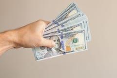 100 dollar anmärkningar i den manliga handen över grå färger Royaltyfria Foton