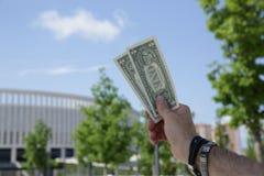 Dollar auf der Rückseite mit einem gesamt-sehenden Augenzeichen in der Hand vor dem hintergrund eines Gebäudes des blauen Himmels lizenzfreie stockfotografie
