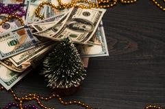 Dollar auf einem schwarzen Hintergrund mit einem Weihnachtsbaum und Spielwaren stockfotografie