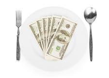 Dollar auf einer weißen Platte mit einer Gabel und einem Löffel Lizenzfreies Stockfoto