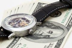 100 Dollar auf weißem Hintergrund mit Armbanduhren Stockbilder