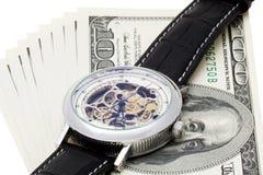 100 Dollar auf weißem Hintergrund mit Armbanduhren Stockbild
