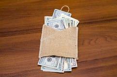 Dollar av olika värden i säck Fotografering för Bildbyråer