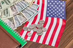 Dollar banknote with coins and flag, notepad, pen on table Royalty Free Stock Images