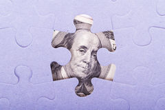 Dollar Banknote between Puzzle Pieces Royalty Free Stock Photo