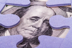Dollar Banknote between Puzzle Pieces Stock Images