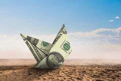 Bad times in business . Mixed media. Dollar banknote ship in desert as symbol for financial crisis . Mixed media Stock Photos