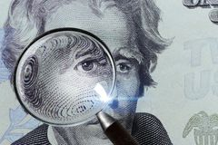 Dollar banknote under a magnifying glass is being inspected on white background Stock Photography