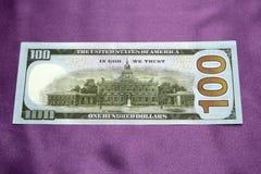 100 Dollar Banknoten auf einem purpurroten Hintergrund Stockfotos