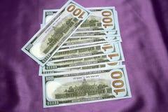 100 Dollar Banknoten auf einem purpurroten Hintergrund Stockbilder