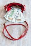100 Dollar Banknoten fallen heraus von der roten Handtasche Stockfotografie