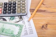 Dollar-Banknoten mit Bleistift und Taschenrechner auf Einkommen-Bericht Lizenzfreie Stockbilder