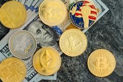 Dollar banknotes and assorted cryptocurrency coins Stock Photos