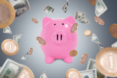 Dollar Banknotes and Coins Falling Around Piggy Bank. Group of one hundred dollar banknotes and coins flying or falling around pink piggy bank on dark background Stock Photos