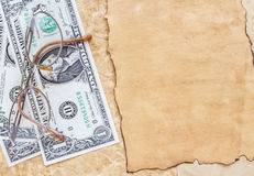 Dollar banknotes and eyeglasses on old paper background Royalty Free Stock Photography