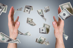 Dollar Banknotes Falling on Young Male Hands Royalty Free Stock Image