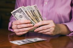Dollar banknotes in female hands. Woman counts dollar bills, banknotes in female hands. Counting money on the table Royalty Free Stock Photography