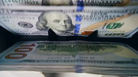 Dollar banknotes are getting stacked by the counting device. HD stock video footage