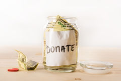 Dollar banknotes in glass jar with donate lettering and red heart symbol Stock Photos