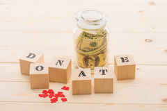 Dollar banknotes in glass jar and wooden cubes with donate lettering Royalty Free Stock Image
