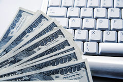 Dollar banknotes on a keyboard Royalty Free Stock Photography