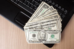 Dollar banknotes on laptop keyboard Royalty Free Stock Photo