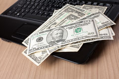 Dollar banknotes on laptop keyboard Stock Image