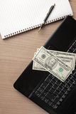 Dollar banknotes on laptop keyboard Royalty Free Stock Images