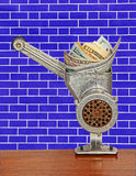 Dollar banknotes in meat grinder on blue brick wall background.M Stock Image