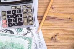 Dollar Banknotes with Pencil and Calculator on Earning Report. Finance and business concept, hundred dollar banknotes with pencil and calculator on earning Stock Photos