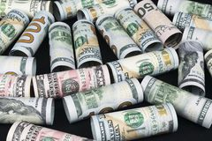 Dollar. Dollar banknotes roll in other positions. American US currency on black board. American dollar banknote rolls Stock Photo