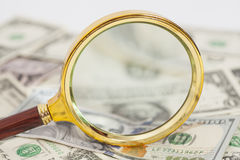 Dollar banknotes under magnifying glass Stock Photos